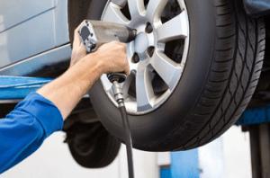 mechanic working on car wheel