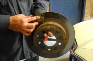 brake pads being shown by a mechanic