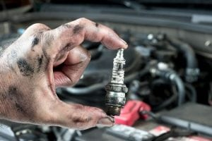 a sparkplug over being hold by a mechanic
