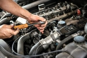 man using socket wrench for engine repair in coconut creek